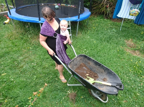 Pushing a wheel barrow with Jai in a ring sling